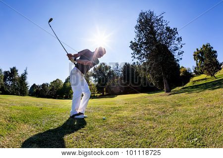 Golf sport: male caucasian golfer hits a shoot from the fairway. Summer season, sunny day.