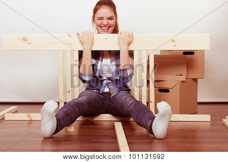 Happy Woman Moving In Assembly Furniture At Home.