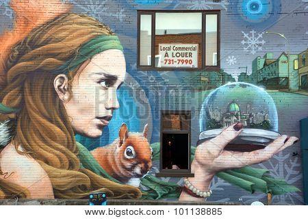 Street art woman hold a snow globe