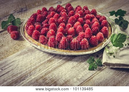 Tart with raspberries on a wooden background with space for text.