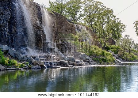 Three waterfalls with reflections on lake near the forest