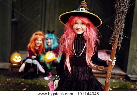 Smiling girl in Halloween attire holding broom and looking at camera