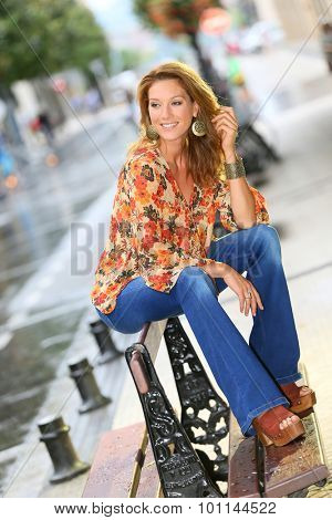 Attractive trendy woman sitting on public city bench