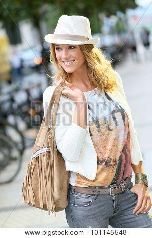 Trendy woman with hat walking in city street