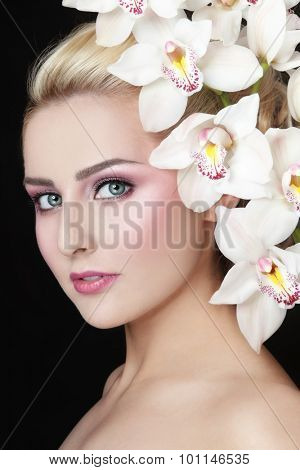 Portrait of young beautiful woman with stylish make-up and white orchid in her hair
