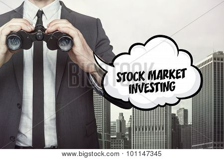 Stock market investing text on speech bubble with businessman holding binoculars