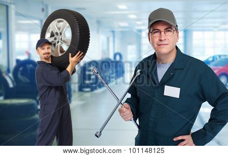 Smiling repairman with tire wrench in car repair service.