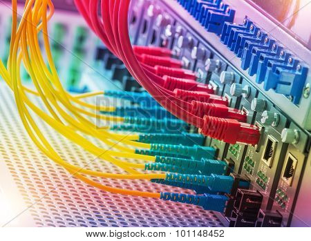 Fiber Optic cables connected to an optic ports and Network cables connected to ethernet ports.
