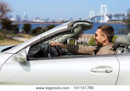 travel, tourism, transport, leisure and people concept - happy man driving cabriolet car over river and tokyo rainbow bridge background