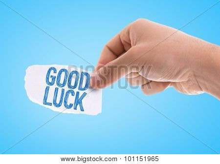 Piece of paper with the word Good Luck with blue background