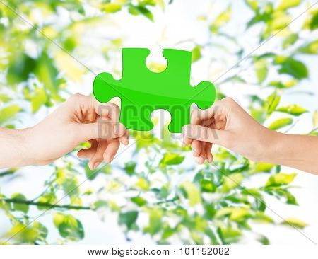 nature, ecology, energy saving, people and environment concept - close up of couple hands with green puzzle over natural background