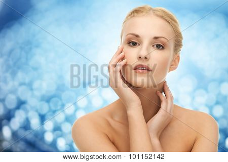beauty, people and health concept - beautiful young woman touching her face and neck over blue lights background