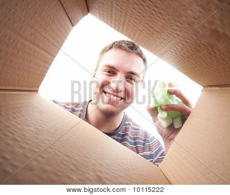 Man Throwing Packing Polyfoam Into Cardboard Box