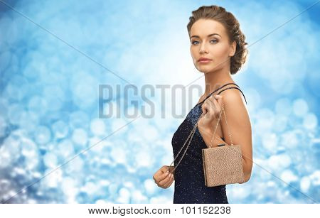 people, holidays, luxury and glamour concept - woman in evening dress with small bag over blue lights background