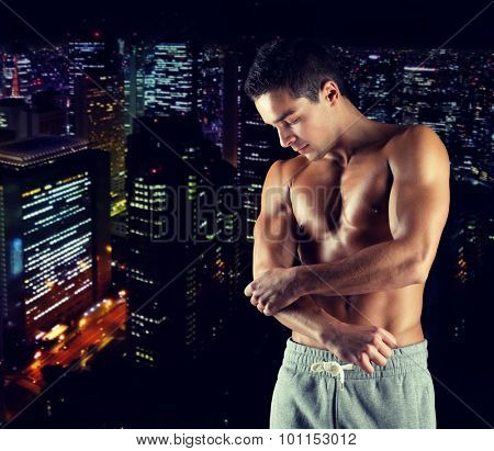 pain, sport, bodybuilding, health and people concept - young male bodybuilder touching injured elbow over night city background