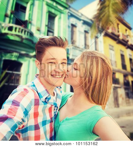 travel, tourism, technology, love and people concept - smiling couple kissing and taking selfie over latin american city street background
