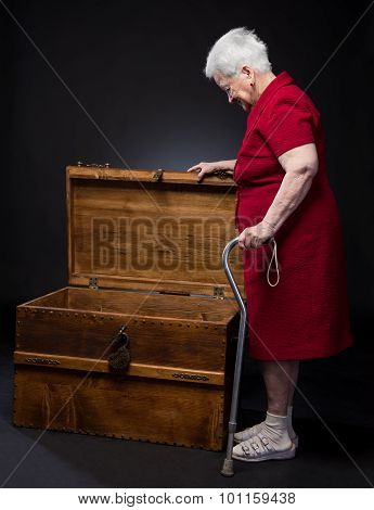 Old Surprised Woman Looking Into  A Big Box