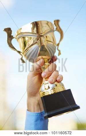 Business champion showing gold cup