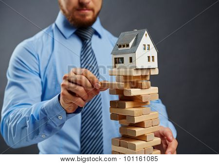 Businessman taking out wooden block from high construction with toy house on its top