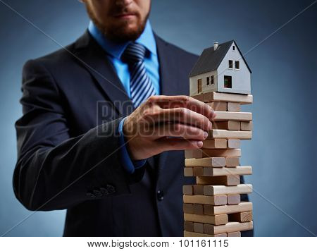 Businessman touching wooden tower with house on its top