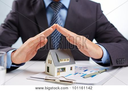 Realtor with open palms over toy house