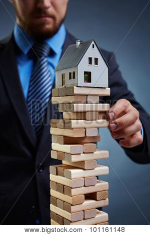 Businessman touching tower from small wooden blocks with house on its top