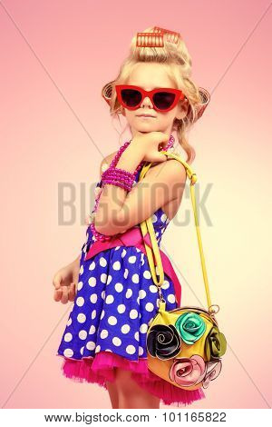 Fashionable little girl in her mother's hair curlers and pin-up sunglasses. Kid's fashion, cosmetics. Pin-up style.