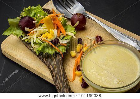 Corn Salad And Red Wine On Black Table Spoon On The Floor.