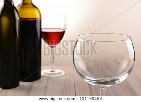 Closeup of an empty wineglass with bottles and full glass in the background. Horizontal still life with warm tones and light to dark background lighting.