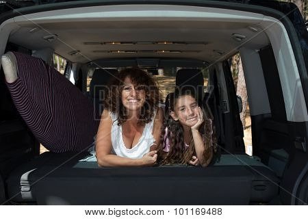 Mother And Daughter In  Trunk Of Car Ready To Depart For Holidays