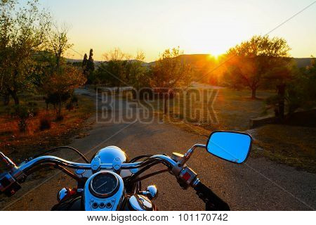 Motorcycle On The Edge Of The Road At Sunset