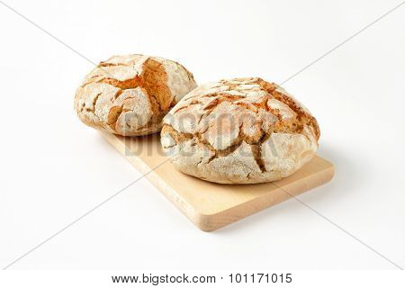 two fresh loaves of bread on wooden cutting board