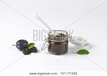 jar of fresh plum jam and plums on white background