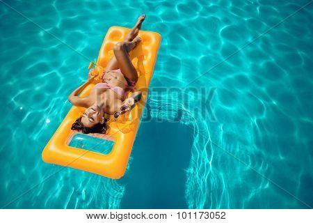 Portrait of a beautiful woman sunbathing on mattress in swimming pool