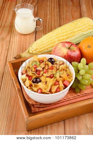 Corn flakes bowl in tray with apple, orange, grapes and corn with milk jar on wooden background
