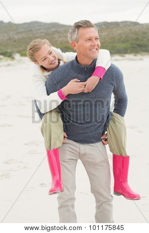 Father giving his daughter a piggy back at the beach
