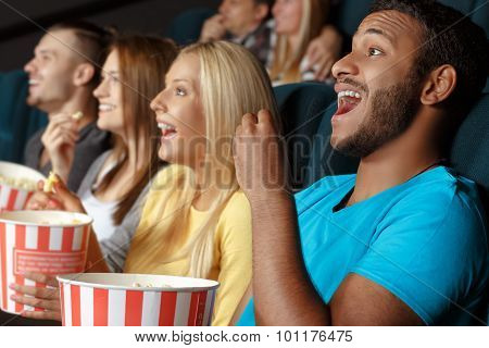 Friends laughing during a movie
