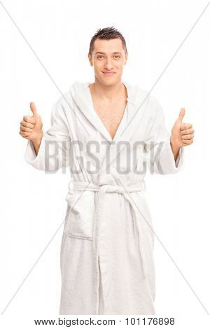 Happy young man in a white bathrobe giving two thumbs up and looking at the camera isolated on white background