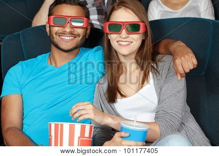 Happy couple watching a movie at the cinema