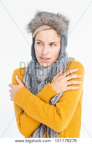 Attractive blonde wearing a warm hat while shivering