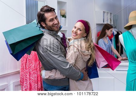 Portrait of smiling couple with shopping bags embracing in clothing store