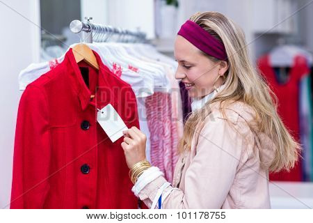 Smiling woman looking at price tag in clothing store