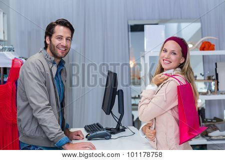 Portrait of smiling cashier and his customer in clothing store