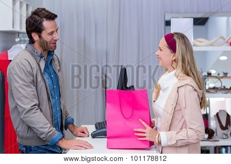 Smiling woman talking to cashier in clothing store