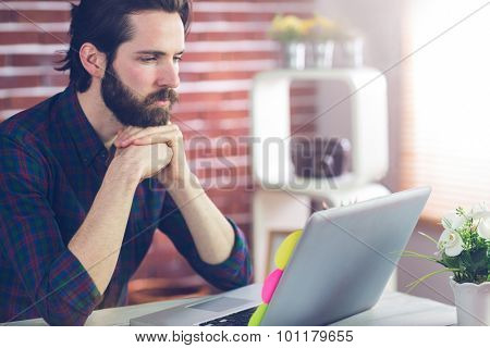 Serious editor with hand clasped using laptop in creative office