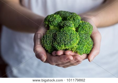 Woman showing fresh green brocolli in close up