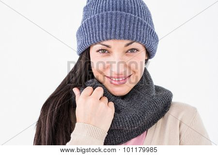 Attractive brunette looking at camera wearing warm clothes on white background