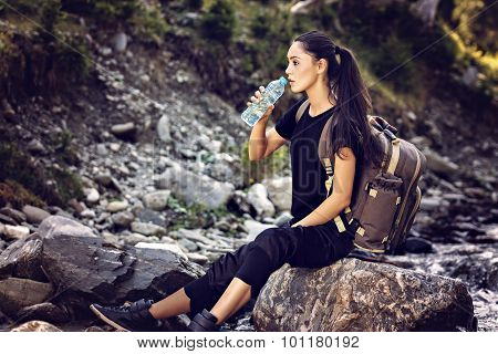Beautiful Woman Resting On A Rock In The River And Drinking Water
