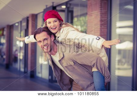 Girlfriend piggy-backing on her boyfriend at the mall