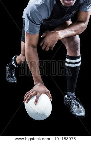 Low section of rugby player holding ball over black background
